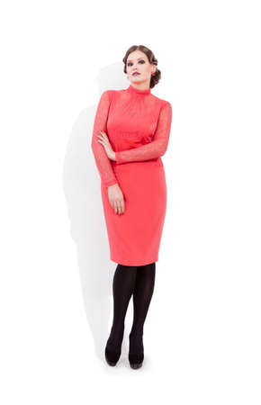 Beautiful woman in red standing next to white background  Stock Photo