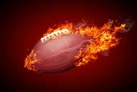 American football ball in fire isolated on dark red background Stock Photo
