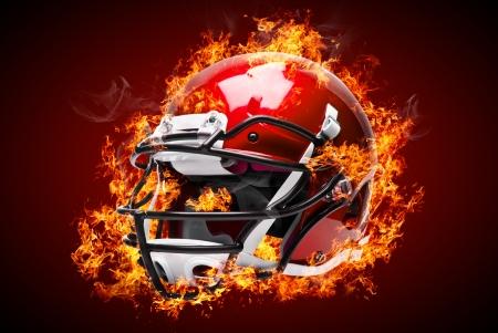 casco rojo: Casco de fútbol americano en el fuego aislado en fondo oscuro Foto de archivo