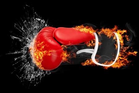 赤いパンチ ボクシング グローブに火災パンチ ガラス上分離の暗い背景