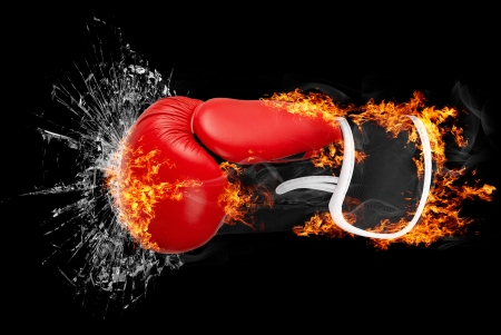 punching: Red punching boxing glove in fire isolated on dark background punching glass  Stock Photo
