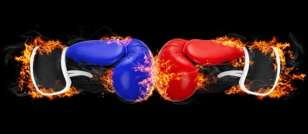 Red and blue boxing gloves in fire punching each other on black background  Фото со стока