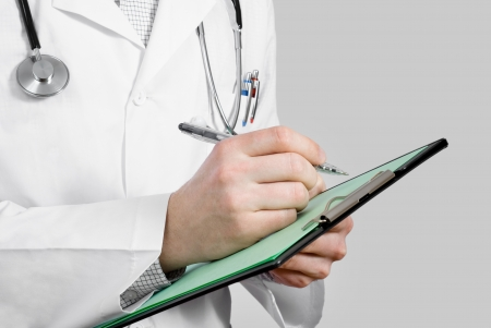Doctor with stethoscope making note on clip board