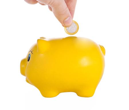Hand putting a coin into piggy bank