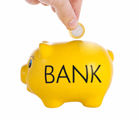 business savings: Hand putting a coin into piggy bank with word Bank