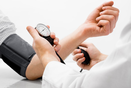 stethoscope exam: Doctor measuring blood pressure - studio shot on white background