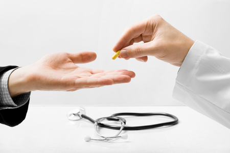 Male doctor giving small pill to patient photo