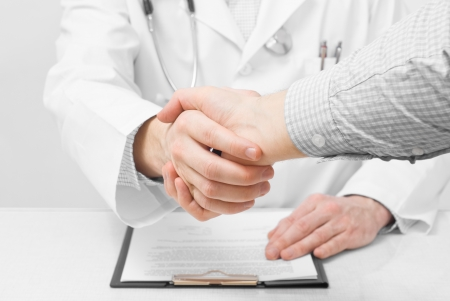 Doctor with stethoscope and clipboard shaking patients hand Stock Photo