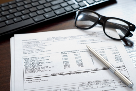 Tax form on the table together with glasses, pen and computer keyboard Stock Photo