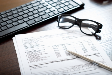 Tax form on the table with glasses, pen and computer keyboard