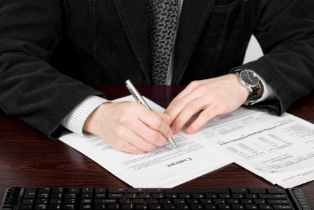 financial official: Businessman filling out contract form. Financial world with business people and everything related to it.