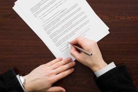 Business man filling out contract with silver pen