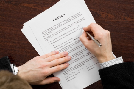 filling out: Businessman filling out contract and signing it
