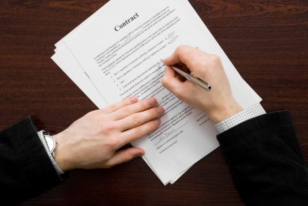 Businessman filling out contract and signing it on the table Stock Photo
