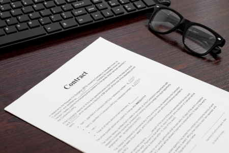 financial official: Contract on the table with glasses and keyboard