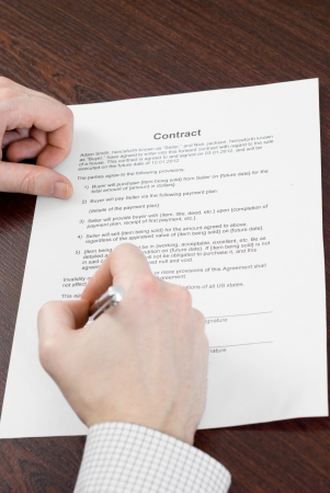 Male signing contract on the table