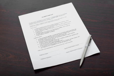Business document with silver pen on brown table photo