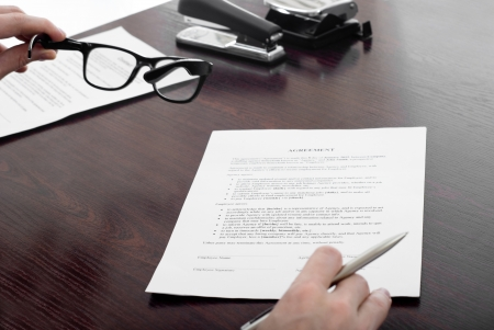 Business man looking though glasses on agreement document Stock Photo