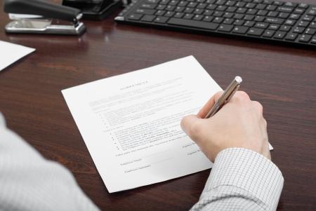 Hombre de negocios llenar contrato en su escritorio Foto de archivo - 24648321