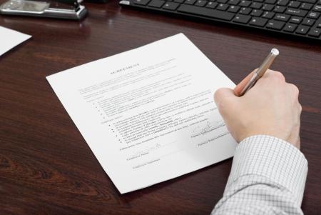 Hombre de negocios llenar contrato en su escritorio Foto de archivo - 24648322
