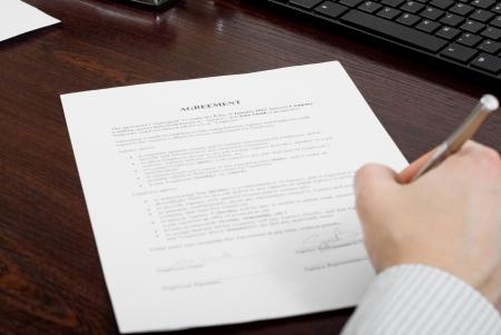 Persona de negocios la firma del contrato en su escritorio Foto de archivo - 24648325