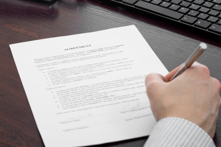 Business person signing contract at his desk Stock Photo