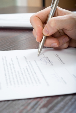 Close up shoot of signing contract by a business person