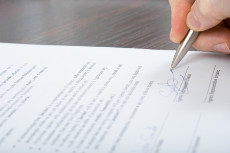 Close up shoot of signing contract by a businessmen with silver pen