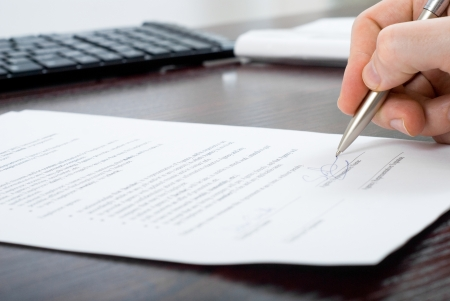 Close up shoot of signing contract by a businessmen with silver pen at his working place