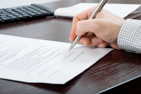 Close up shoot of signing contract by a businessmen at his desk
