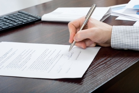 Close up shoot of signing contract by a businessmen at brown desk