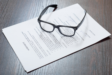Glasses on the table with contract papers Stock Photo