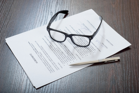 financial official: Glasses on the table with contract papers and silver pen