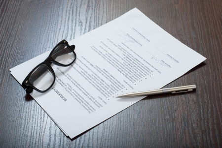 financial official: Contract papers on the table with glasses and silver pen