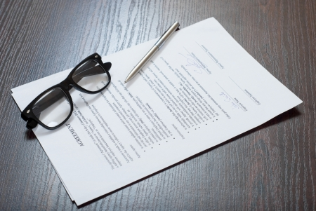Contract papers on the table with glasses and a pen Stock Photo
