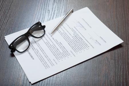 Documentos contractuales en la tabla con gafas y una pluma Foto de archivo - 24648463