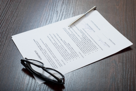 Contract papers on brown table with glasses and silver pen Stock Photo