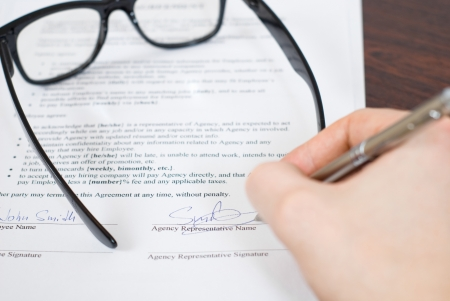 Male signing contract and putting glasses on it Stock Photo