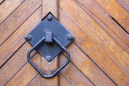 door knob: old black handle on the brown wooden door