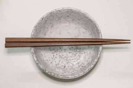 Empty bowl with a pair of brown chopsticks Reklamní fotografie