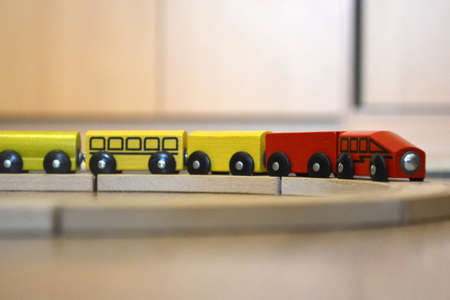 The red-yellow wooden train rides on the toy railway. Toy for preschoolers, developing game Banco de Imagens