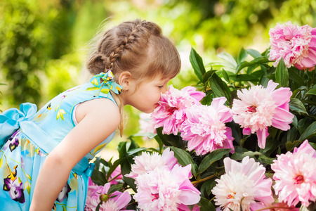 smells: Cute little a girl in a blue dress smells flowers pi-mesons Stock Photo