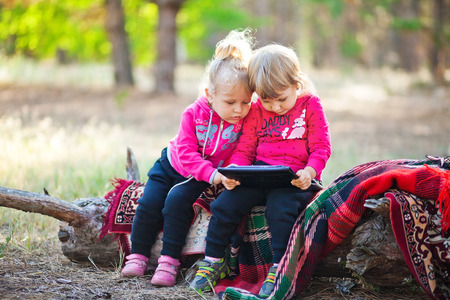 logirl-friends look the animated cartoons at a tablet in forest