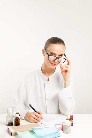 wearing spectacles: the beautiful doctor wearing spectacles write the recipe to the patient