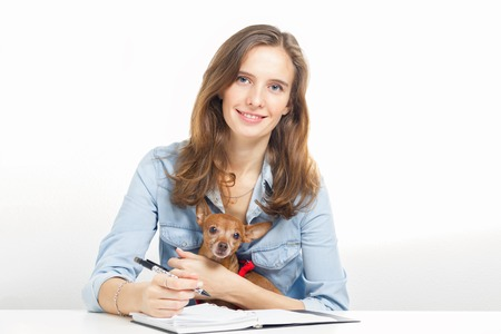 doggie: The girl with a small doggie sits at a table and writes notes to a notebook Stock Photo