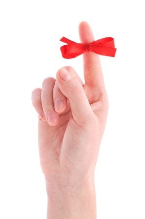 Red bow on finger, isolated on white background photo