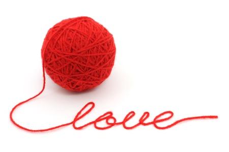 hilo rojo: Bola de hilo con el �amor� la palabra sobre fondo blanco