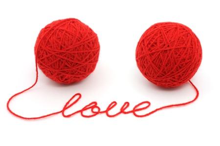 hilo rojo: Bolas de hilo con el �amor� la palabra sobre fondo blanco