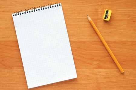 White blank notebook with yellow pencil on a wooden table photo