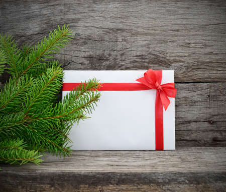 envelope: Christmas tree and gift envelope on wooden background. Stock Photo